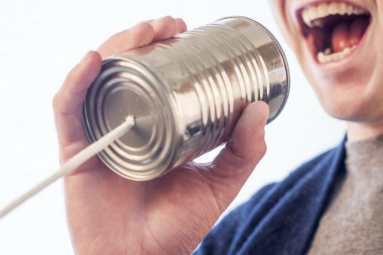 Man shouting down a toy tin can phone