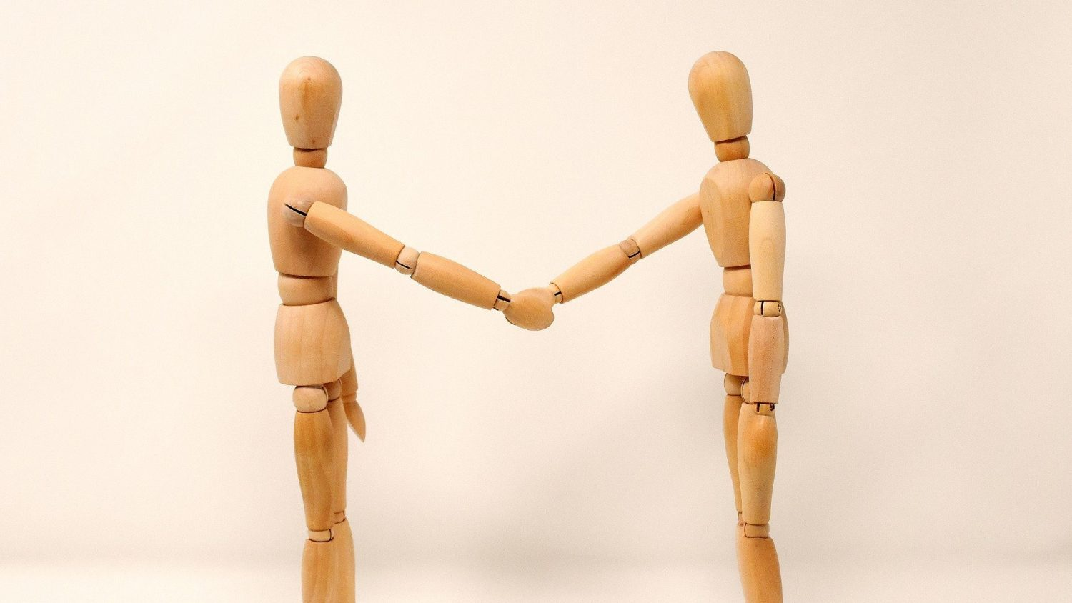 Wooden statues holding hands