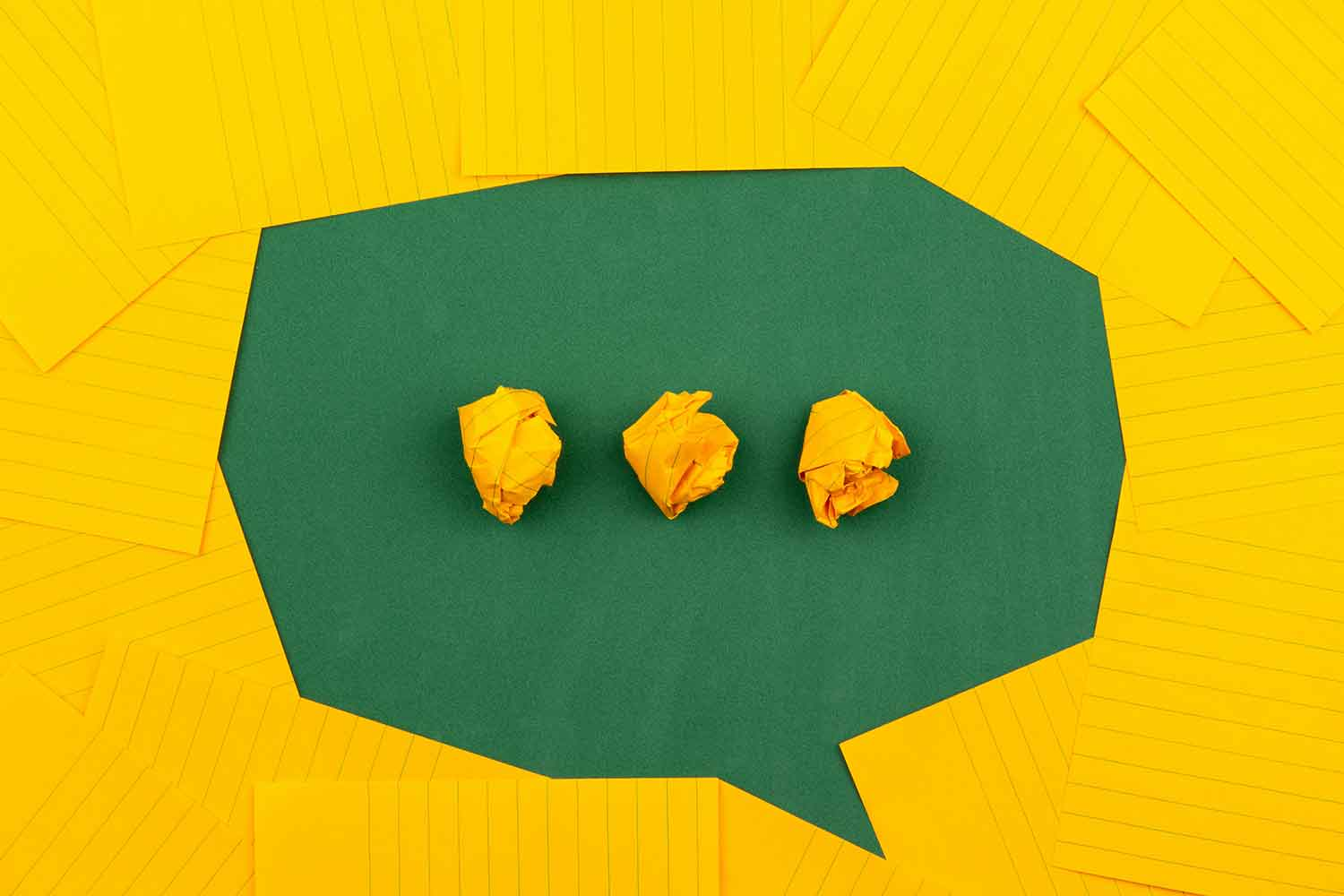 orange sheets of paper lie on a green school board and form a chat bubble