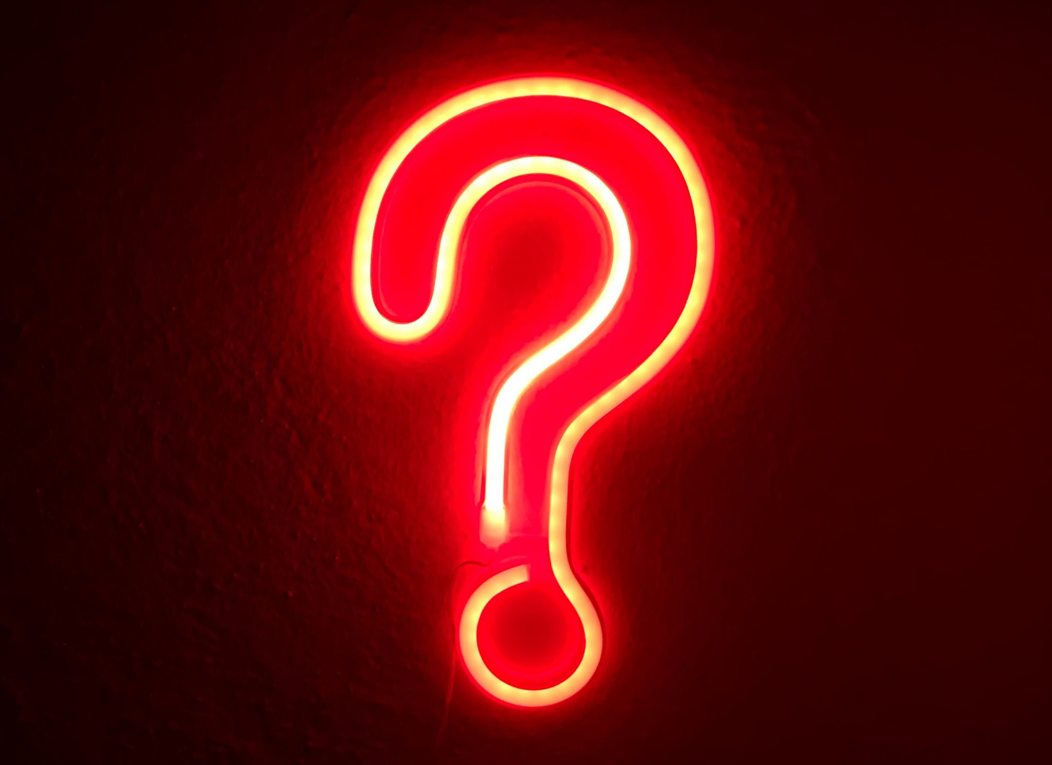 A question mark neon sign in red, glowing against a dak background