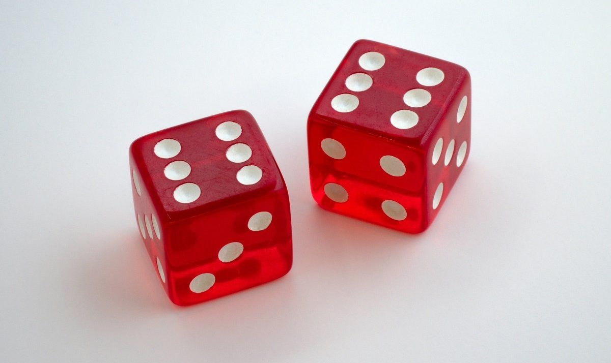 Two red dices on a white table, both showing the number 6
