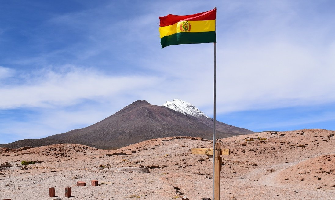 The flag of Bolivia raised in the Bolivian desert with blue skies and a mountain in the background