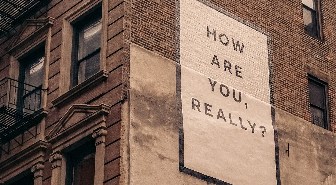 """A brick building with a large white billboard on it saying """"How are you, really?"""""""