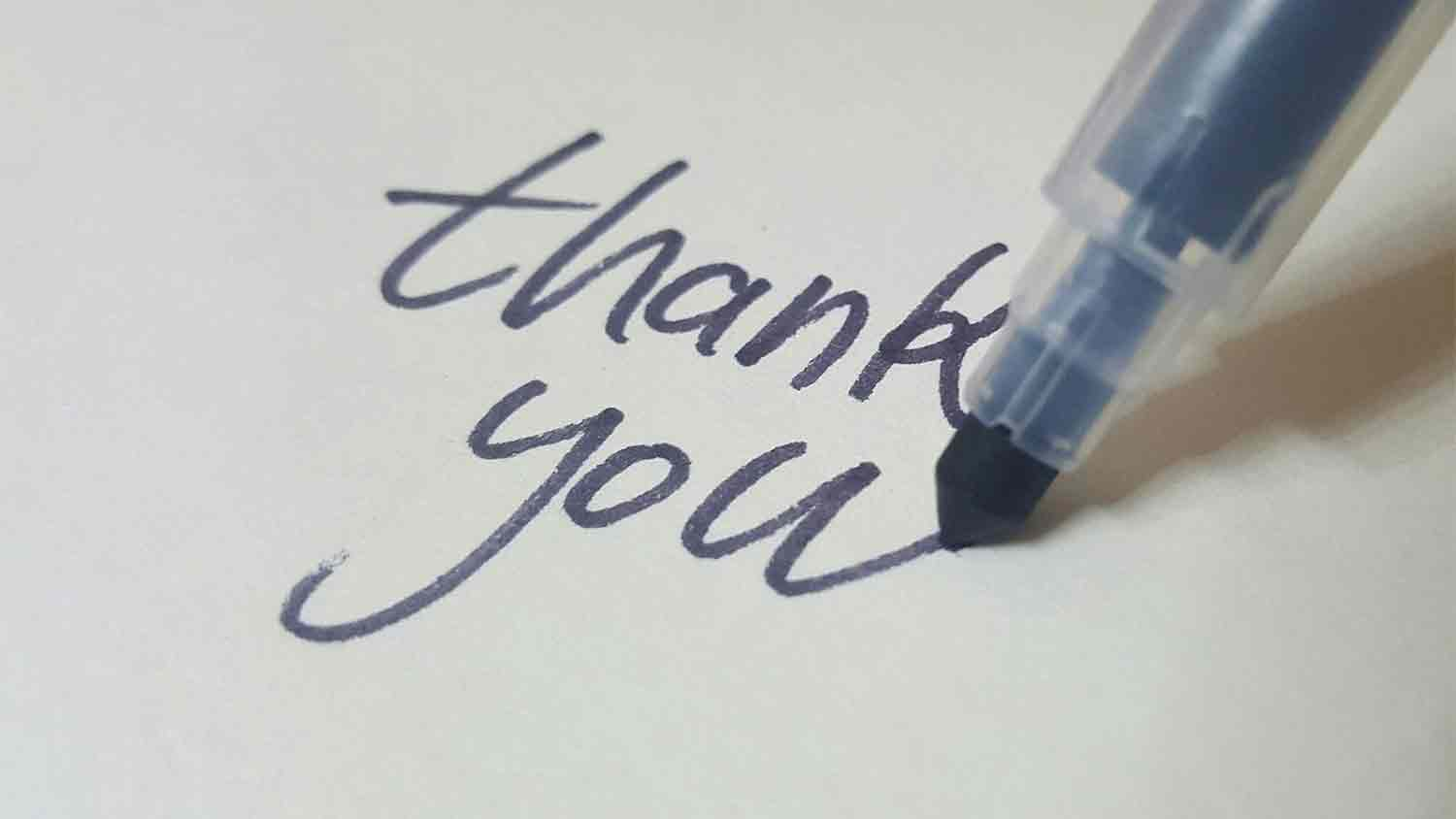 thank you written on card by a thick blue pen