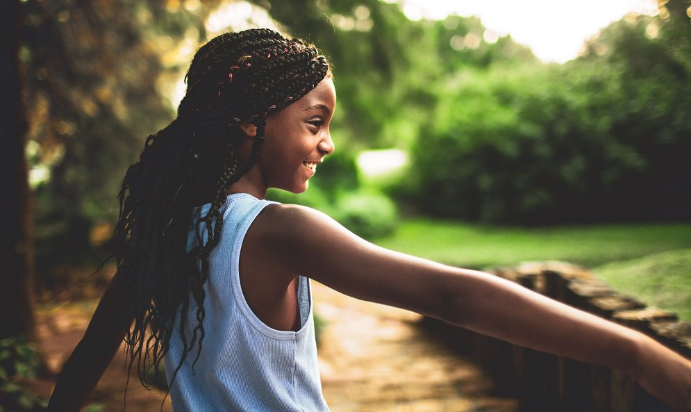 A young black girl in a white tank top in a park