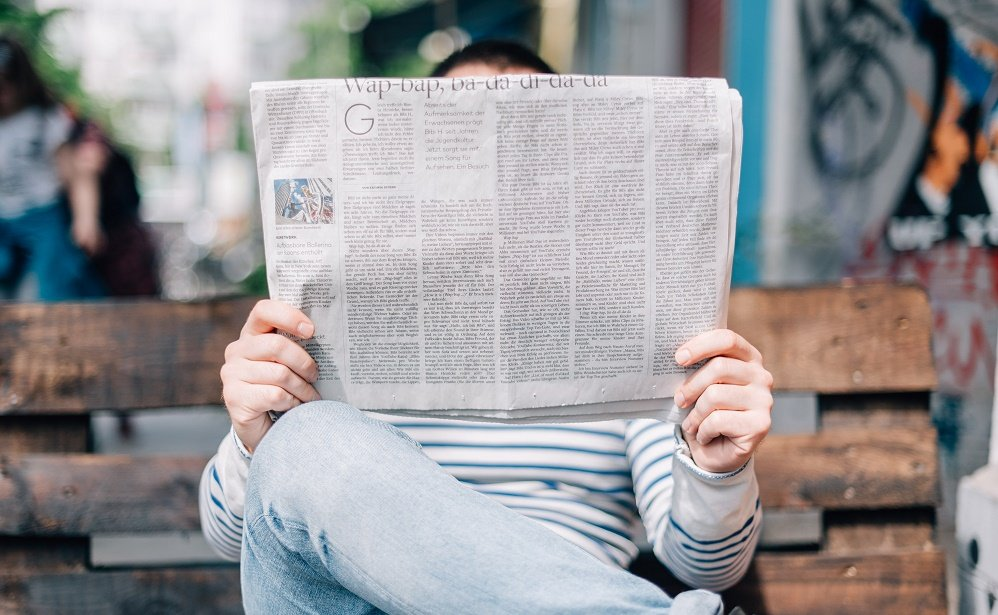 Man in a striped jumper and blue jeans reading a newspaper on a bench