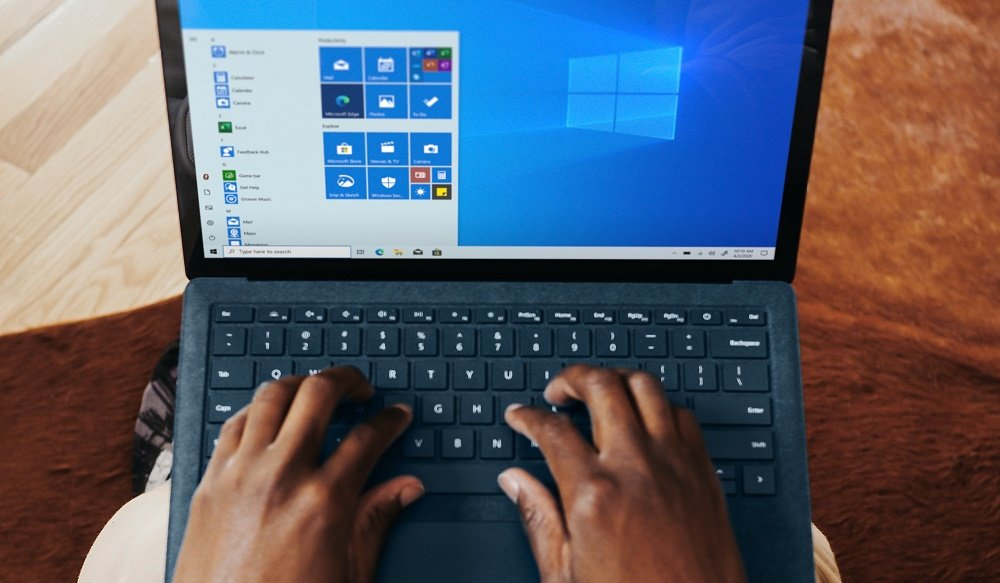 Two black hands using Windows on a laptop balanced on the persons lap laptop