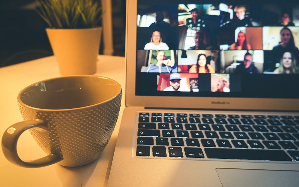 A laptop screen with an ongoing blurred zoom meeting, with a mug next to it