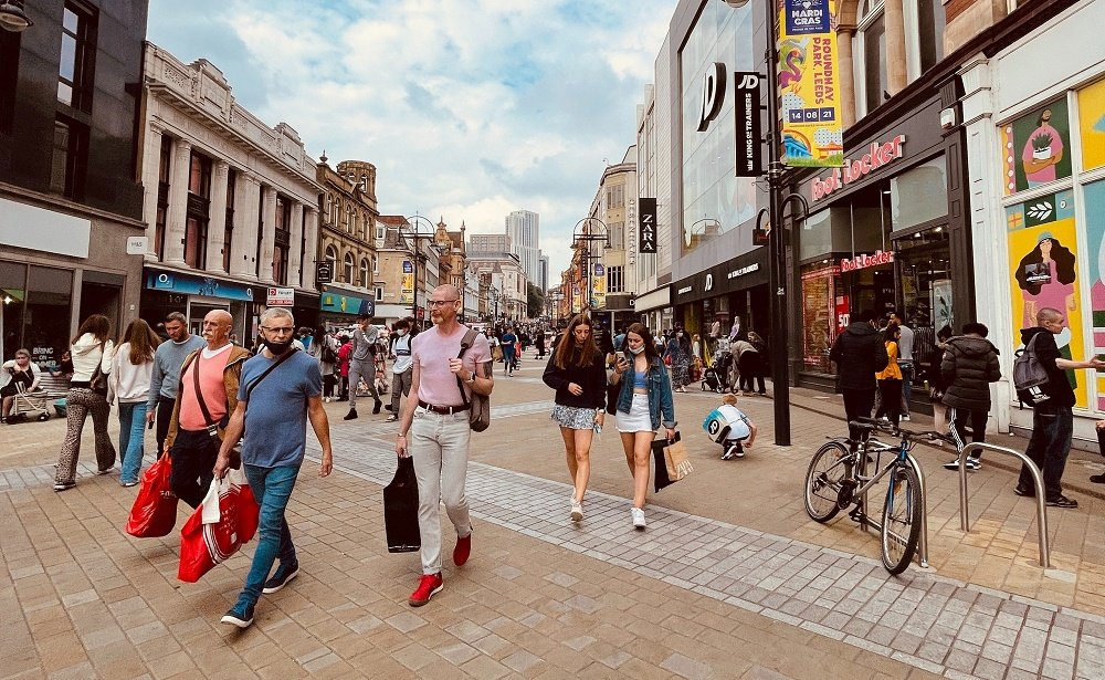People walking down a high street in Leeds during day time