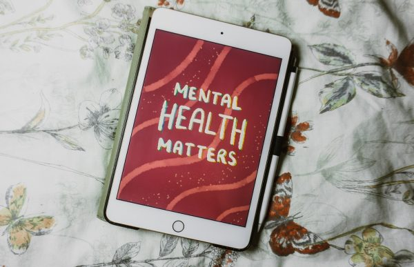 An ipad on a flower patterned bedspread, displaying the message 'Mental health matters'